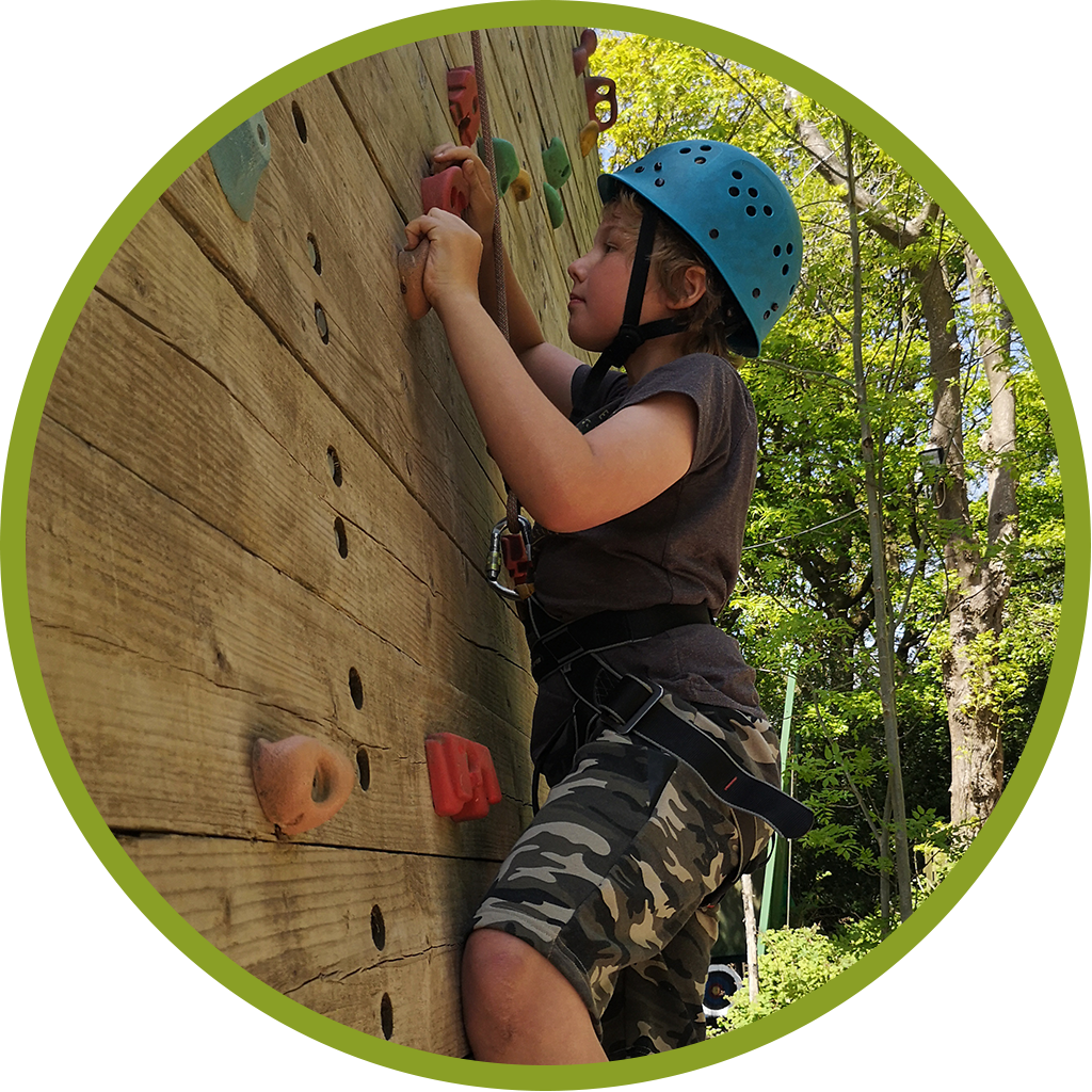 Young boy climbing a climbing wall