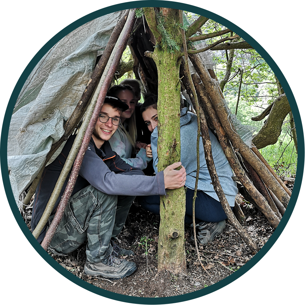 Group of teens in a makeshift shelter in the woods