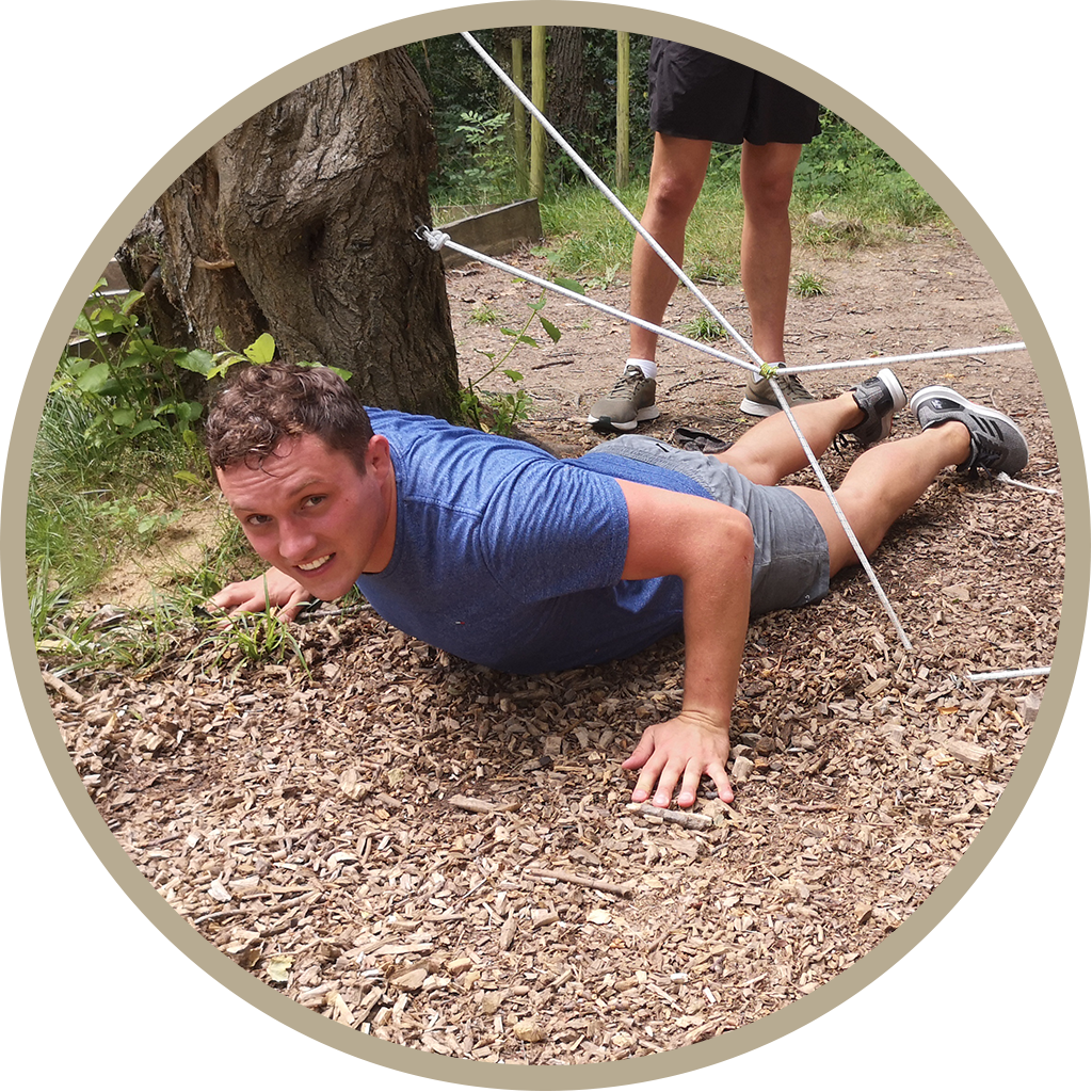 Young man crawling underneath metal ropes